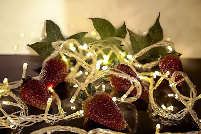 Jordgubbar i mitt av julljus royaltyfria bilder