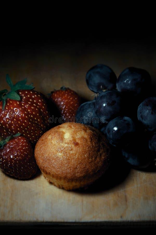 Jordgubbar, kaka och druvor p? tr?br?de royaltyfri bild