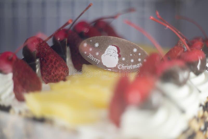 Jordgubbar och Cheery-frukt i jultemat, där krämen piffas över kakor royaltyfri foto