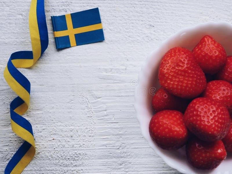 Jordgubbar och svensk flagga på vit bakgrund royaltyfri foto