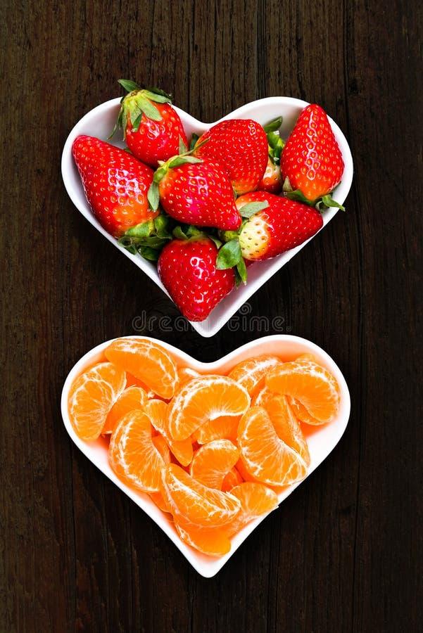 Jordgubbar och tangerinskivor i vita plattor royaltyfri bild