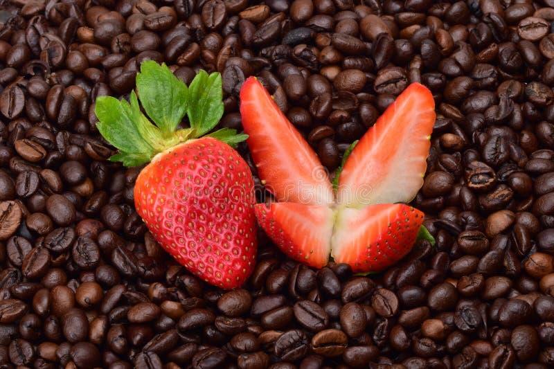 Jordgubbar, snitt in i fyra stycken och ett helt bär av mogna jordgubbar royaltyfri fotografi