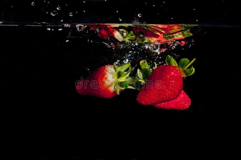 Jordgubbar som plaskar in i vatten arkivbild