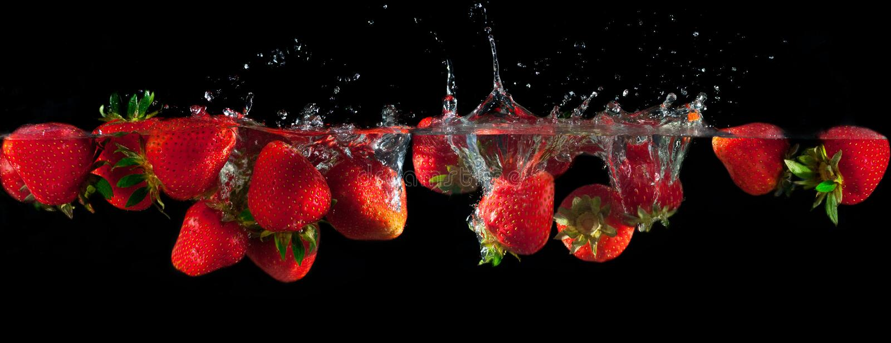 Jordgubbar som plaskar in i vatten royaltyfri bild