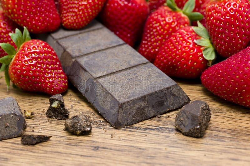 Jordgubbar som rå choklad whooden på, bordlägger royaltyfri foto