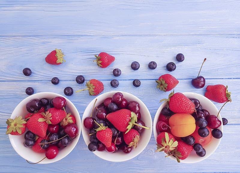 Jordgubbe körsbär, blåbär, aprikos för plattavitaminskörd på en träbakgrund fotografering för bildbyråer