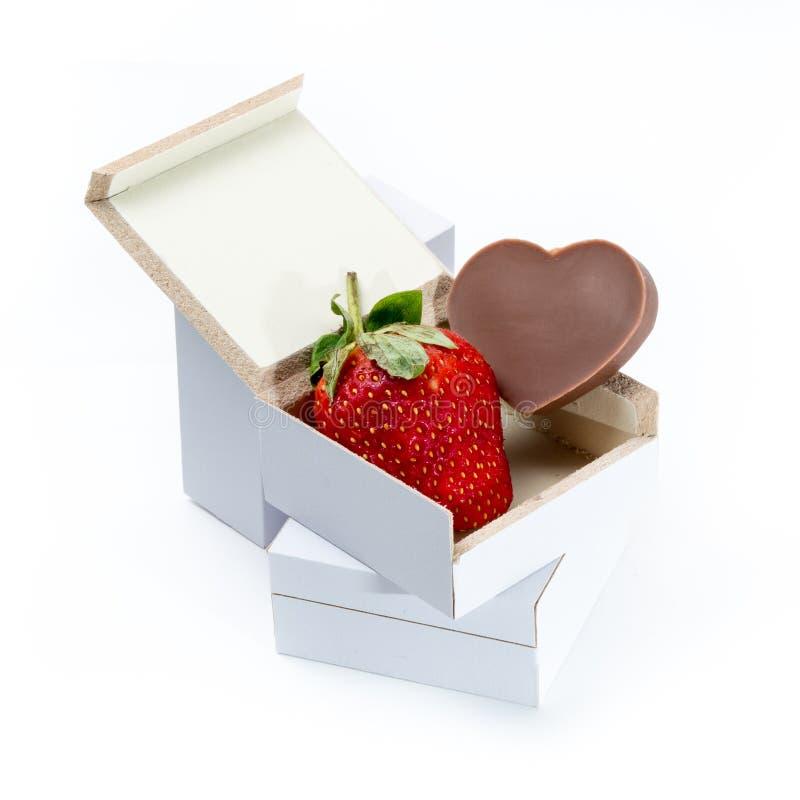 Jordgubbe och Hjärta-formad choklad i en ask på vit bakgrund arkivfoton