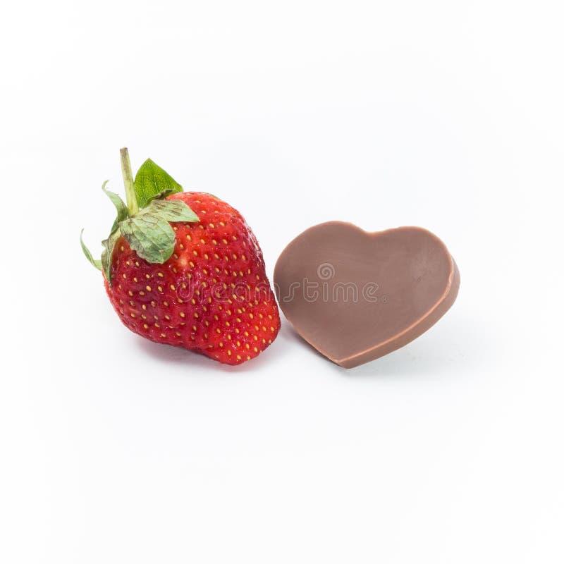 Jordgubbe och Hjärta-formad choklad på vit bakgrund arkivbild