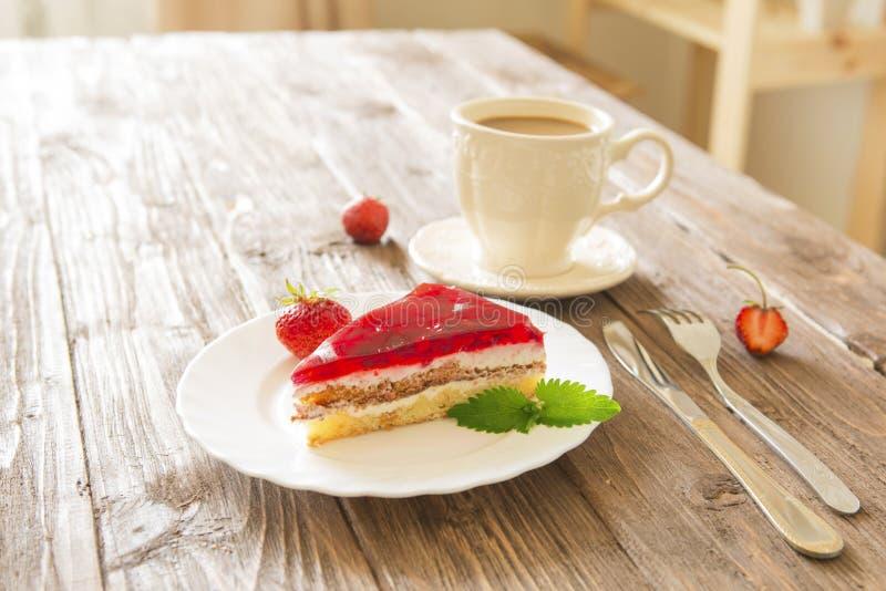 Jordgubbe som är syrlig på plattan med kaffe på trätabellen royaltyfri bild
