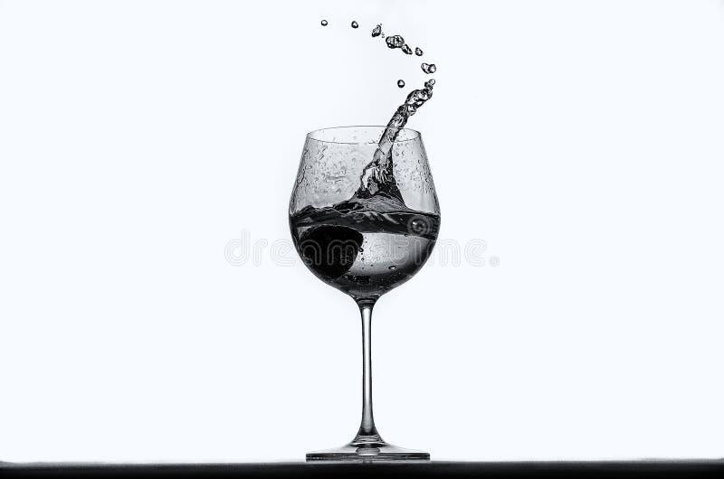 Jordgubbe som faller in i glas av vin royaltyfria bilder