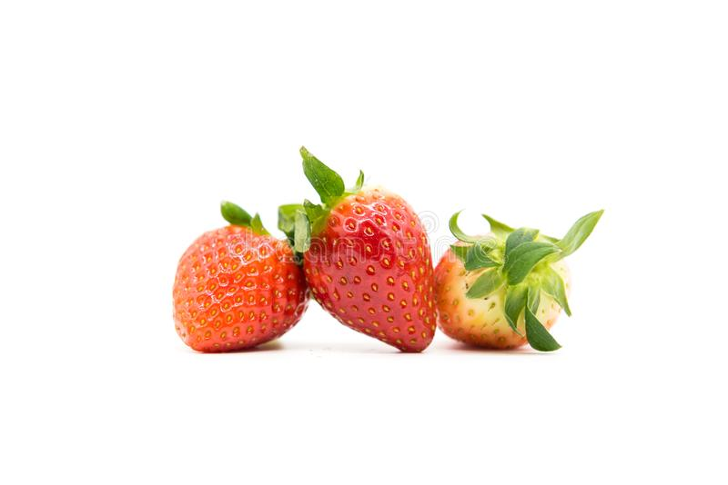 jordgubbe tre är på en vit bakgrund royaltyfria foton