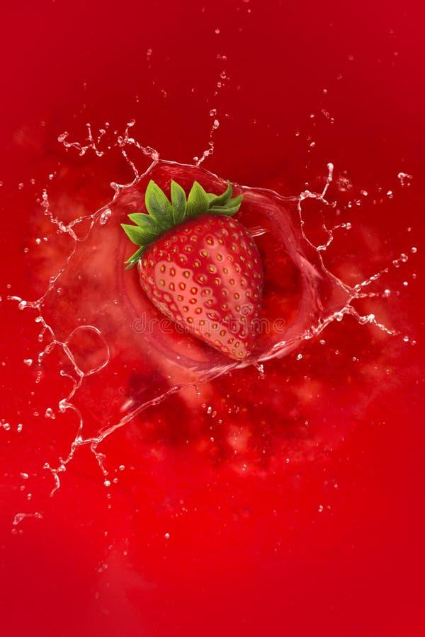 Jordgubbefärgstänk in i fruktsaft royaltyfria foton