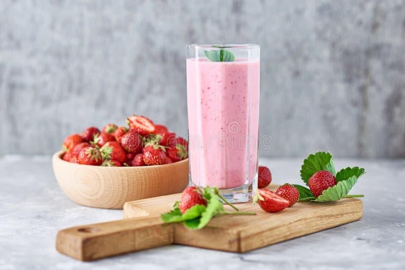 Jordgubbemilkshake i en exponeringsglaskrus och nya jordgubbar med sidor arkivbild