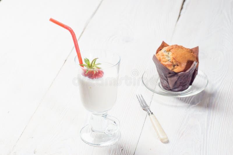Jordgubbemilkshake med den läckra muffin royaltyfria foton