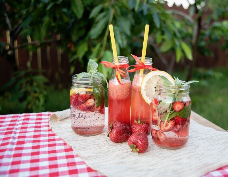 Jordgubben och mintkaramellen ingav detoxvatten jordgubbelemonad med is och mintkaramellen som den förnyande drinken för sommar i royaltyfri fotografi