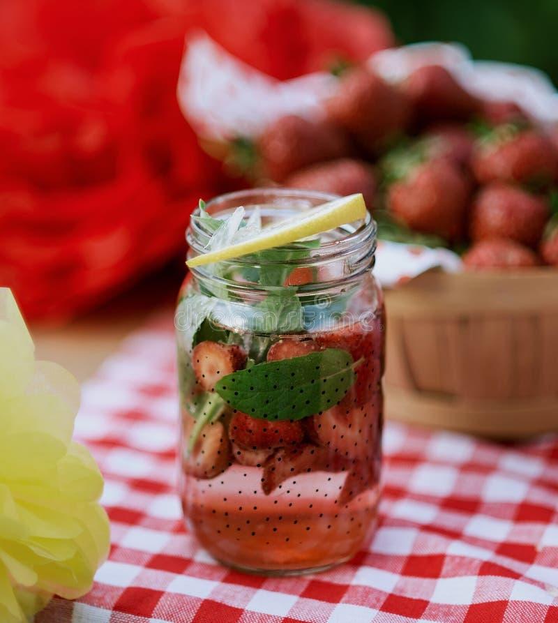 Jordgubben och mintkaramellen ingav detoxvatten jordgubbelemonad med is och mintkaramellen som den förnyande drinken för sommar i arkivfoto