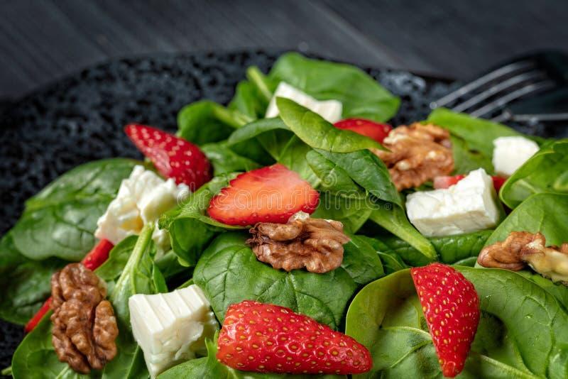 Jordgubbespenatsallad med fetaost, valnötter, olivolja, nolla arkivfoto