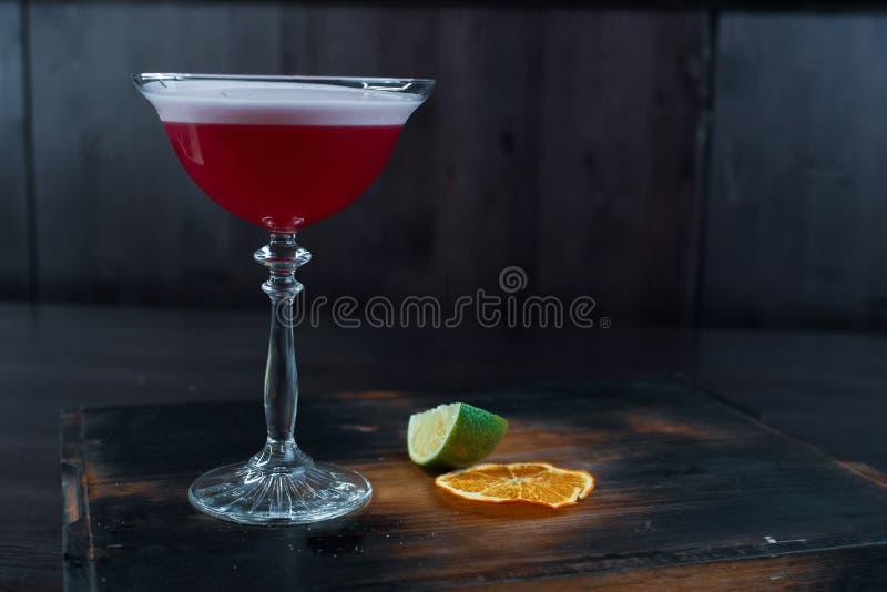 Jordgubbetvå-lager läcker coctail med uppiggningsmedel och vodka med bärlikör med fradga i ett kristallexponeringsglas royaltyfri bild