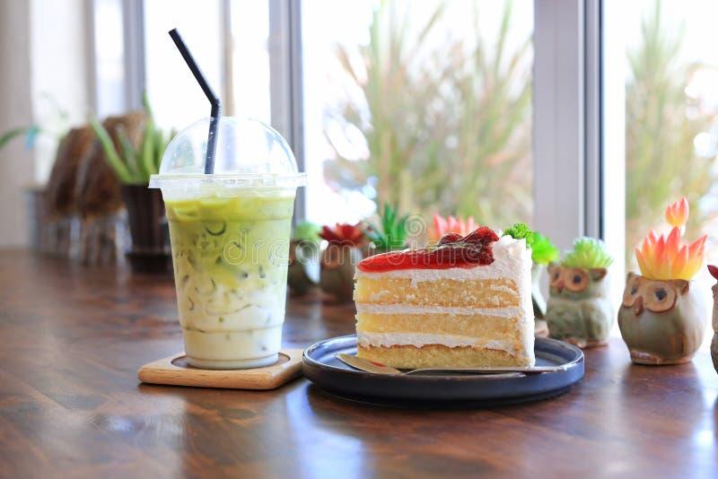 Jordgubbstårta i metallbricka och Iced Mata green tea latte in take-off-koppar på träbord vid kafé arkivfoto