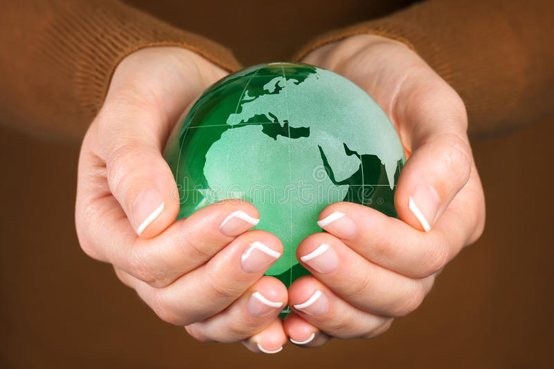 Jordklot för grönt exponeringsglas i hand royaltyfri fotografi