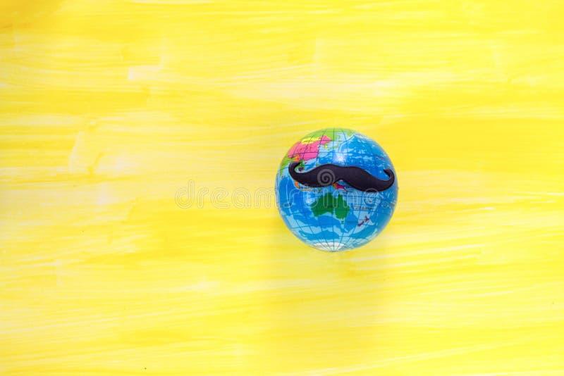Jordklot med en mustasch som firar movember på gul bakgrund royaltyfri fotografi