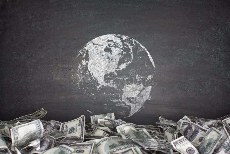 Jordklot med högen av dollarräkningar arkivfoton