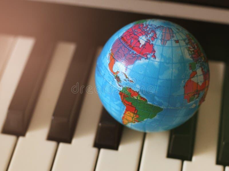 Jordklot på pianotangenterna, en liten modell av jorden royaltyfria bilder