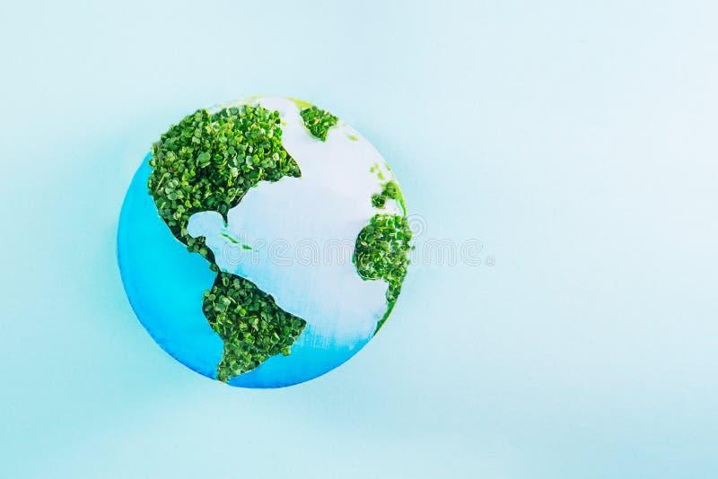 Jordmodellen som göras av pappers- och ny gräsplan, spirar collage på blå bakgrund Idérikt begrepp för grön planet brown räknad d arkivbild