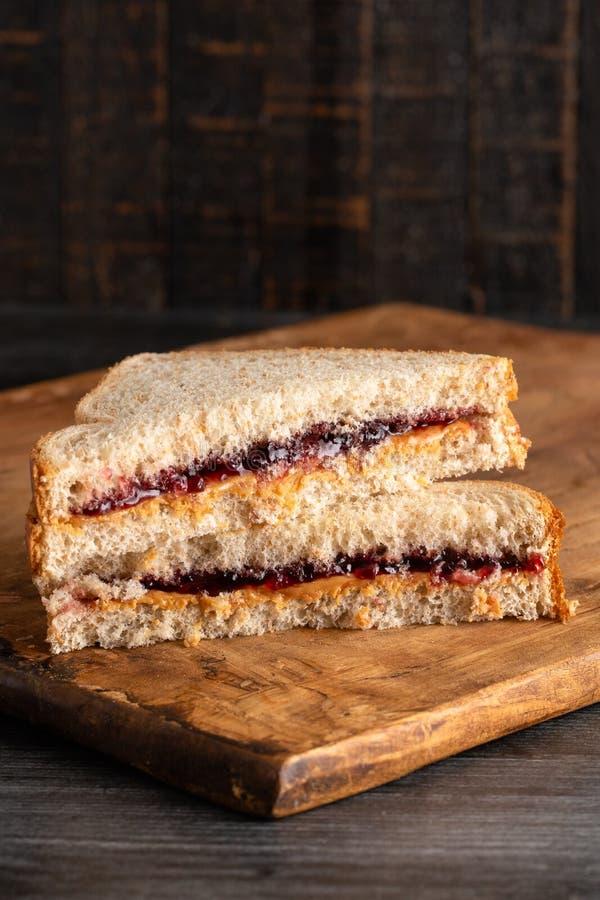 Jordnötsmör och druva Jelly Sandwich på en träskärbräda royaltyfri fotografi