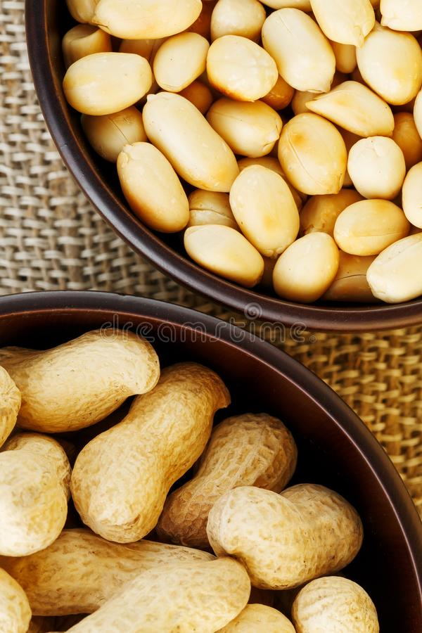 Jordnötter i skalet och den skalade närbilden i koppar Grillade jordnötter i deras skal och skalade mot en brun torkduk royaltyfria foton