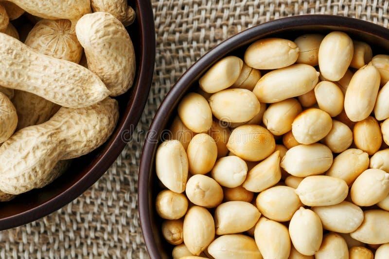 Jordnötter i skalet och den skalade närbilden i koppar Grillade jordnötter i deras skal och skalade mot en brun torkduk royaltyfri bild