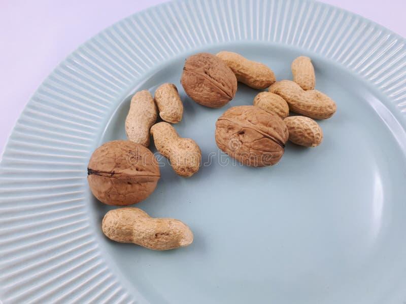 Jordnötter och valnötter på den gröna plattan arkivfoton