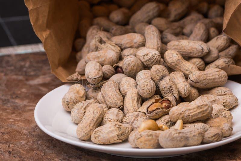 Jordnötter som hälls ut ur en brun pappers- påse royaltyfri bild