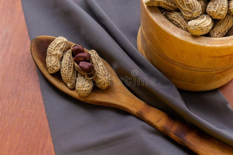 Jordn?ten med skalar och skalar i en bunke bredvid ett tr?bestick och bordduk arkivbild