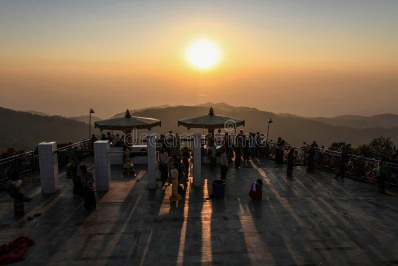 Jordningen av den Kyaiktiyo pagoden som är bekant som guld-, vaggar också på solnedgången, det måndag tillståndet, Myanmar royaltyfria bilder