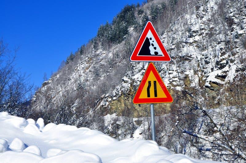 Jordskredriskväg och tecken för vägtrångt pass royaltyfria foton