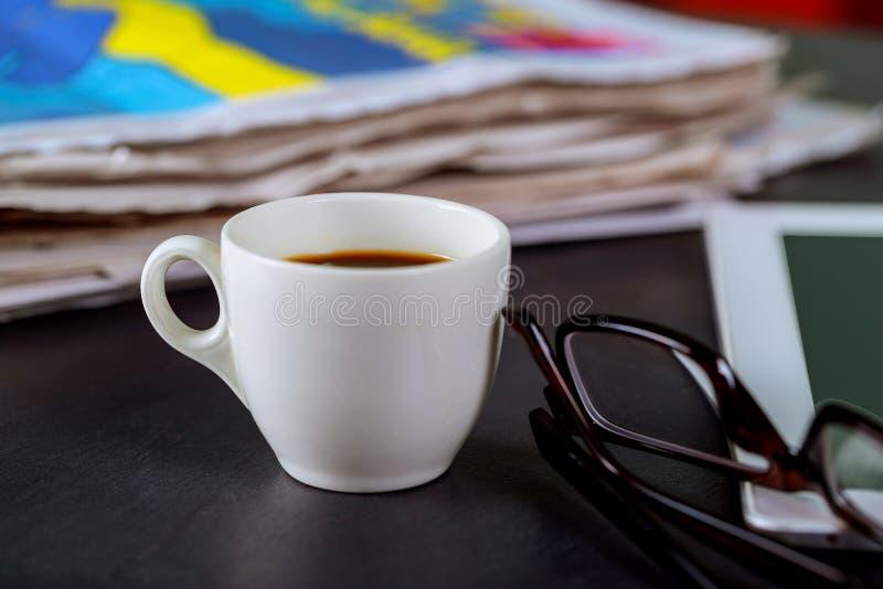 Jornais e copo de café, vidros de leitura e bloco de notas foto de stock