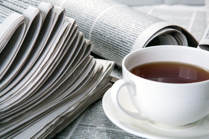 Jornais e um copo do chá na tabela imagem de stock