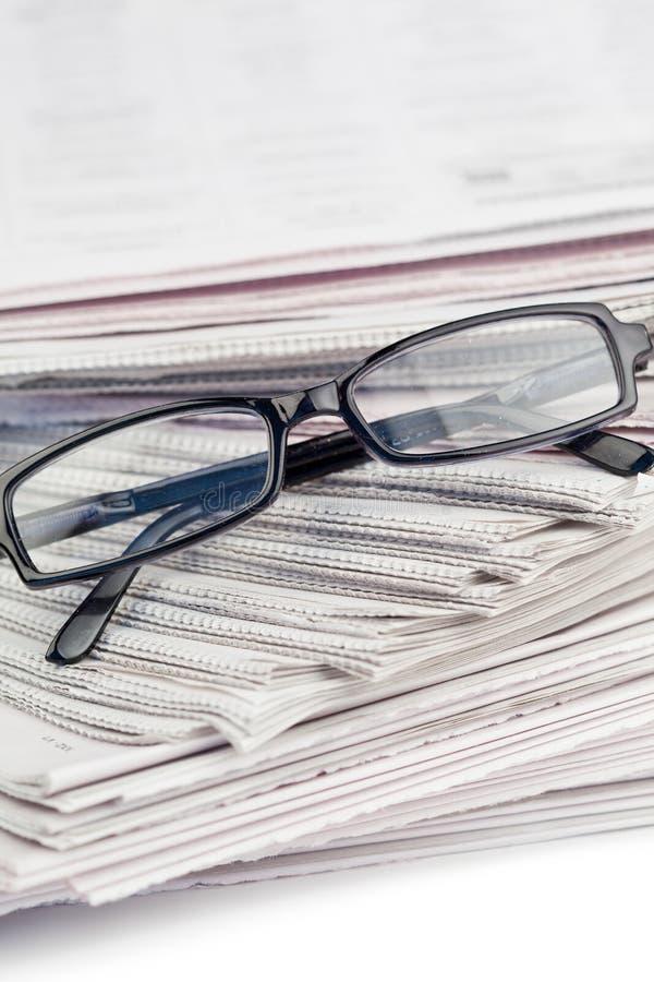 Jornais e vidros pretos fotos de stock royalty free