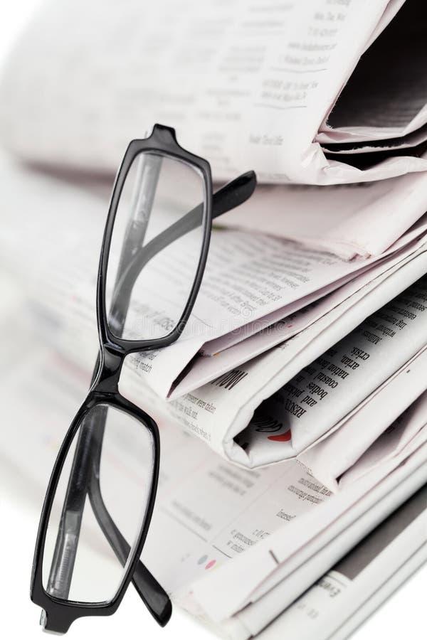 Jornais e vidros pretos imagens de stock royalty free