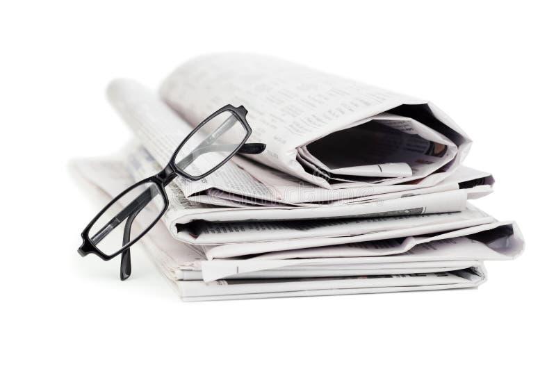 Jornais e vidros pretos imagem de stock