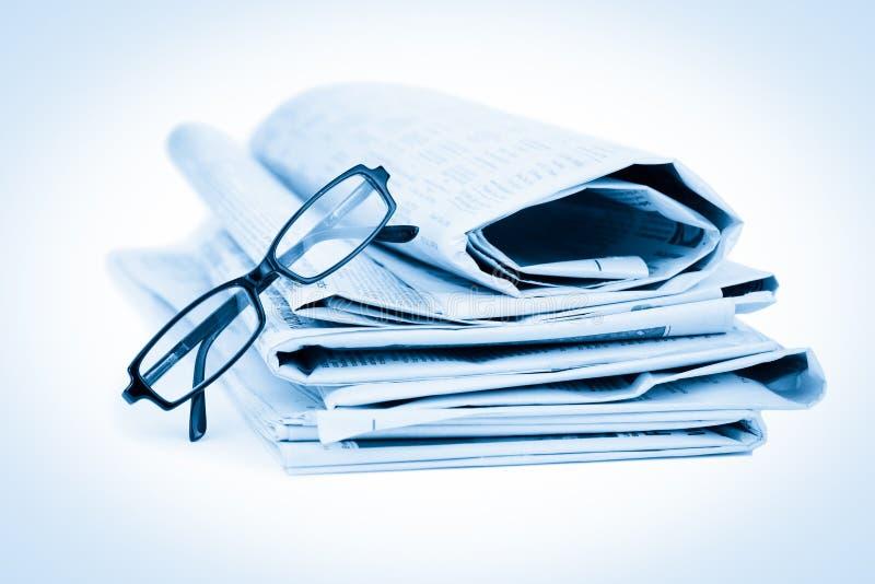 Jornais e vidros pretos fotografia de stock