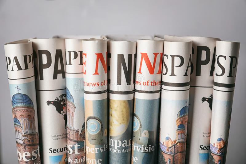 Jornais rolados no fundo cinzento fotografia de stock royalty free