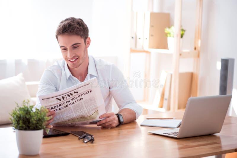Jornal alegre da leitura do homem fotografia de stock