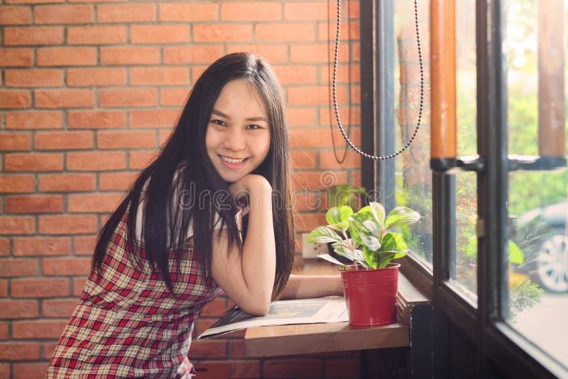 Jornal asiático da leitura da mulher no escritório e sorriso como o fundo imagem de stock royalty free