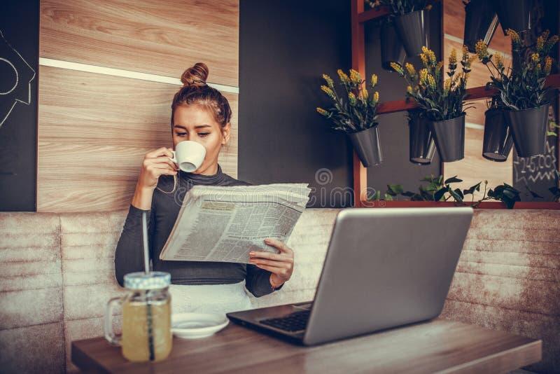 Jornal bonito da leitura da jovem mulher e café bebendo dentro fotografia de stock