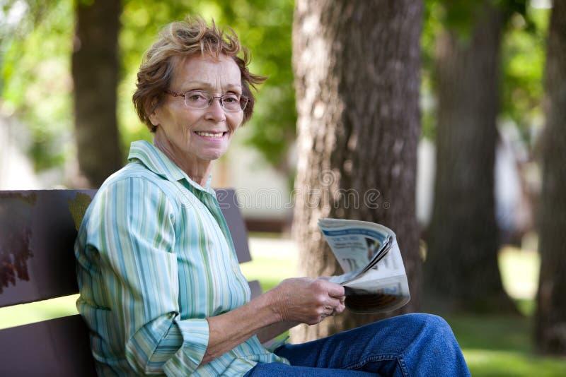 Jornal da leitura da mulher no parque fotografia de stock royalty free