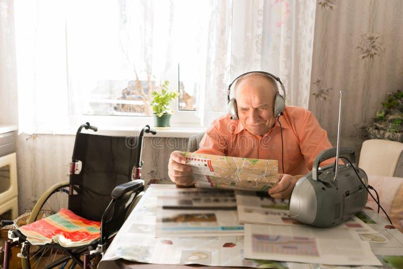 Jornal da leitura do ancião ao escutar no rádio fotografia de stock