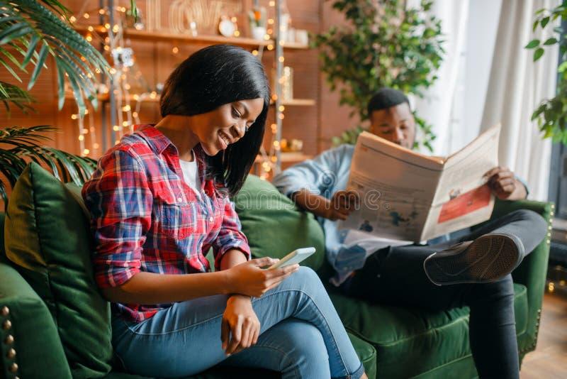 Jornal da leitura do homem negro, sua mulher que usa o telefone fotos de stock
