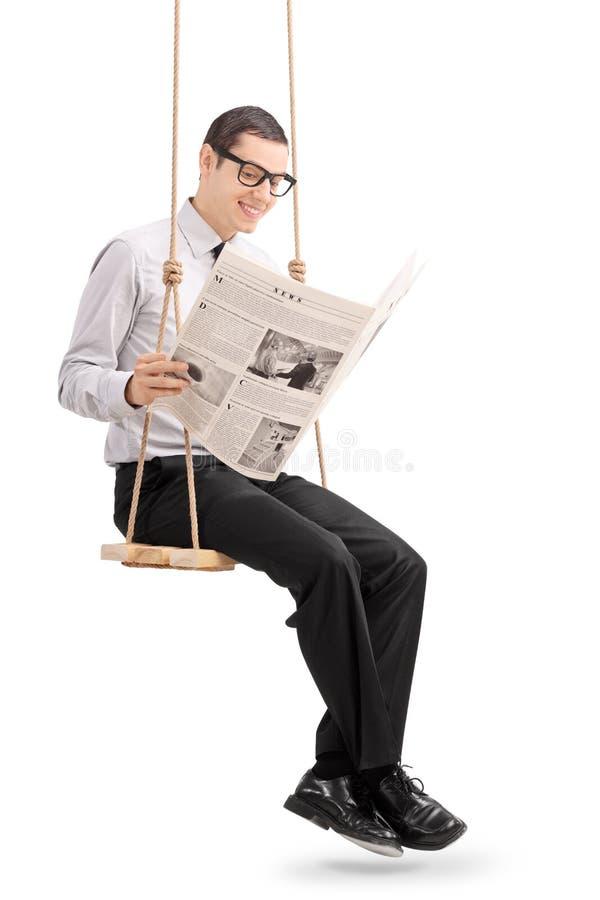 Jornal da leitura do homem novo assentado em um balanço fotografia de stock